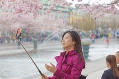 Azjatycka dziewczyna różowię suknię bierze selfie wśród pięknego blo Zdjęcie Stock