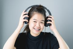 Azjatycka dziewczyna słucha muzyka od czarnych hełmofonów w czarnej przypadkowej sukni W wygodnym i dobrym nastroju fotografia royalty free
