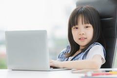 Azjatycka dziewczyna u?ywa laptop i u?miech kamera obrazy stock