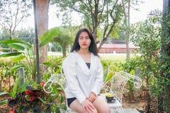 Azjatycka dziewczyna w białym żakiecie siedzi czarną filiżankę kawy w jej ręce na białej ławce i umieszcza pod ranku światłem Obrazy Royalty Free