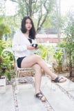 Azjatycka dziewczyna w białym żakieta obsiadaniu i mienie czarna filiżanka coffe w jej ręce na białej ławce pod rankiem zaświeca Fotografia Royalty Free