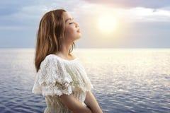 Azjatycka dziewczyna w białym stroju relaksuje i cieszący się zmierzch na plaży obrazy royalty free