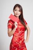 Azjatycka dziewczyna w chińskiej cheongsam sukni z czerwoną kopertą Zdjęcie Stock