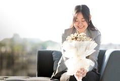 Azjatycka dziewczyna w kostiumu obsiadaniu przy dużym nadokiennym uśmiechem szczęśliwie z obraz stock