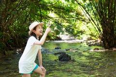 Azjatycka dziewczyna w lesie przy strumieniem, ślicznym małej dziewczynki studiowaniem i lea, fotografia stock