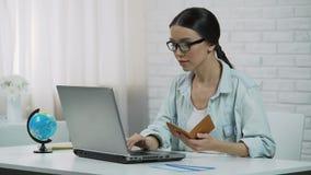 Azjatycka dziewczyna wchodzić do paszportowych dane w laptopie, rezerwuje wycieczkę turysyczną przy agencją podróży zbiory