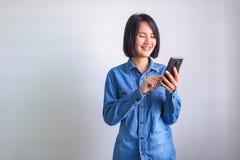 Azjatycka dziewczyna z błękitnym koszulowym lewej ręki mienia telefonem obraz stock