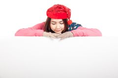 Azjatycka dziewczyna z czerwonych bożych narodzeń spojrzenia kapeluszowym puszkiem odpoczywa jej podbródek na bla Zdjęcia Stock