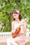 Azjatycka dziewczyna z ukulele gitarą plenerową Fotografia Stock