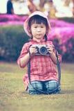 Azjatycka dziewczyny mienia rocznika filmu kamera w ogródzie Rocznika pictur Obrazy Royalty Free