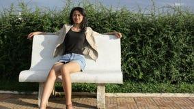 Azjatycka dziewczyny obsiadania banka ławka samotnie zbiory wideo