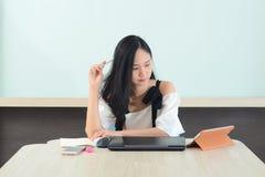 Azjatycka kobieta analizuje pracę z laptopem i książkami w biurze obrazy royalty free
