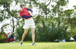 Azjatycka kobieta bawić się golfowego kołyszącego kija golfowego dla teeing daleko w kursie Fotografia Stock
