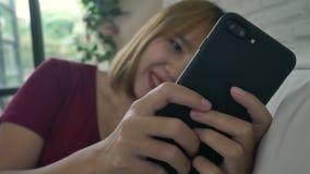 Azjatycka kobieta bawić się smartphone podczas gdy kłamający na domowej kanapie w jej żywym pokoju zbiory