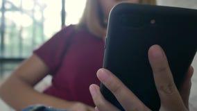 Azjatycka kobieta bawić się smartphone podczas gdy kłamający na domowej kanapie w jej żywym pokoju zbiory wideo