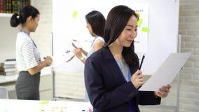 Azjatycka kobieta biznesowa trzymająca długopis i papier patrząca na kamerę podczas spotkania zdjęcie wideo