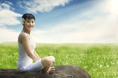 Azjatycka kobieta cieszy się outdoors siedzieć na skale przy łąką przeciw niebieskiemu niebu Obrazy Royalty Free