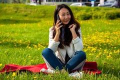 Azjatycka kobieta dzwoni telefonem w lato parku na zielonej trawie zdjęcie stock