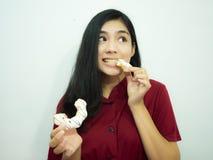 Azjatycka kobieta i pączek Fotografia Royalty Free