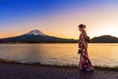 Azjatycka kobieta jest ubranym japońskiego tradycyjnego kimono przy Fuji górą Zmierzch przy Kawaguchiko jeziorem w Japonia obrazy royalty free