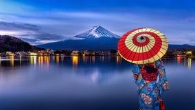 Azjatycka kobieta jest ubranym japo?skiego tradycyjnego kimono przy Fuji g?r?, Kawaguchiko jezioro w Japonia zdjęcia royalty free