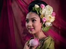 Azjatycka kobieta jest ubranym Tajlandzkiego tradycyjnego smokingowego ręki mienia lotosu fl zdjęcia royalty free