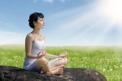 Azjatycka kobieta medytuje outdoors na skale przy łąką przeciw niebieskiemu niebu Obrazy Royalty Free