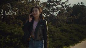 Azjatycka kobieta opowiada na telefonie komórkowym w parku zdjęcie wideo