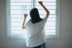 Azjatycka kobieta patrzeje coś na okno i depresja czuciowego smucenie i migrenę w sypialni obrazy royalty free