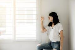 Azjatycka kobieta patrzeje coś na okno i depresja migrenę i uczucia nieobecnego pamiętającego w sypialni obrazy stock