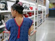 Azjatycka kobieta pcha wózek na zakupy przez domu elektrycznego urządzenia strefy fotografia royalty free