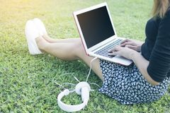 Azjatycka kobieta pisać na maszynie Tajlandzką klawiaturę laptop i obsiadanie na zielonej trawie relaksować Zdjęcia Royalty Free