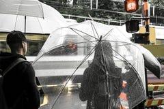 Azjatycka kobieta pod przejrzystym koloru parasolem z kroplami deszcz zdjęcie royalty free