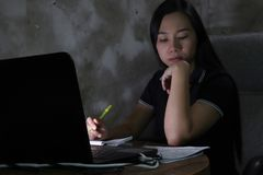 Azjatycka kobieta pracuje od domowego póżno przy nocą - pracuje w biednym oświetleniowym pojęciu zmroku światło niektóre hałas i  zdjęcia royalty free