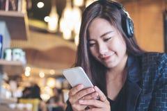 Azjatycka kobieta słucha muzyka z hełmofonem i patrzeje mądrze telefon z czuć szczęśliwy i relaksuje w nowożytnej kawiarni obraz stock