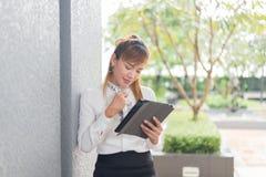 Azjatycka kobieta siedzi laptop w biurowym tle i bawić się zdjęcia stock