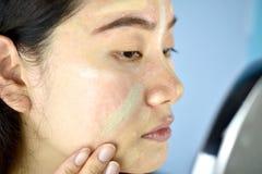 Azjatycka kobieta stosuje kosmetyka makeup i u?ywa kolor korekci concealer zdjęcie stock