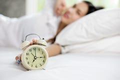 Azjatycka kobieta szczęśliwa budził się i obracający daleko budzika ma Zdjęcia Stock