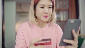 Azjatycka kobieta używa smartphone kupuje online zakupy kartą kredytową w żywym pokoju podczas gdy odzież puloweru obsiadanie na  zbiory wideo