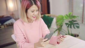 Azjatycka kobieta używa smartphone kupuje online zakupy kartą kredytową w żywym pokoju podczas gdy odzież puloweru obsiadanie na  zbiory