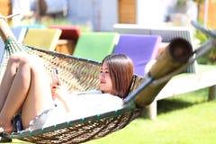 Azjatycka kobieta używa smartphone na ściąga bawić się naturalny tło zdjęcie stock