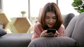 Azjatycka kobieta używa smartphone w jej żywym pokoju podczas gdy kłamający na domowej kanapie zbiory