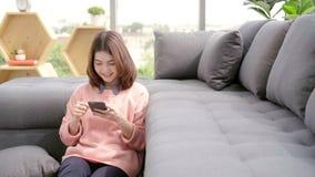 Azjatycka kobieta używa smartphone w jej żywym pokoju podczas gdy kłamający na domowej kanapie zdjęcie wideo