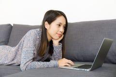 Azjatycka kobieta używa laptop na kanapie Obraz Royalty Free
