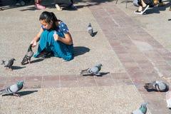 Azjatycka kobieta w błękit sukni kuca żywieniowych gołębie w Pratu Tha Zdjęcia Royalty Free