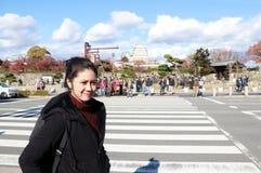 Azjatycka kobieta w czarnej ubraniowej pozyci obok drogi i crosswalk z out skupiamy się turysty fotografia stock
