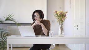 Azjatycka kobieta w eyeglasses pracuje z laptopem w białym ministerstwo spraw wewnętrznych zbiory