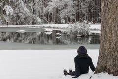 Azjatycka kobieta w kapeluszowym obsiadaniu w śniegu zdjęcia royalty free