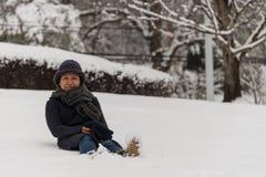 Azjatycka kobieta w kapeluszowym obsiadaniu w śniegu zdjęcia stock