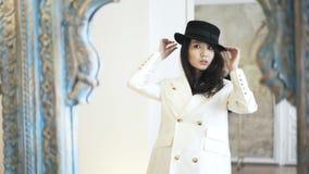Azjatycka kobieta w kapeluszu próbuje na żakiecie w sklepie i bawić się z jej włosy zbiory wideo